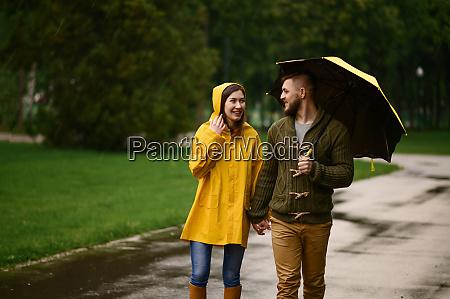 liebespaar mit sonnenschirmen geht in park