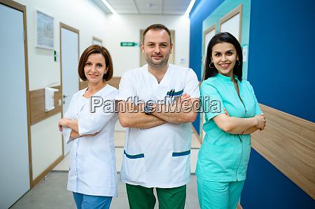 drei laechelnde AErzte stehen im klinikflur