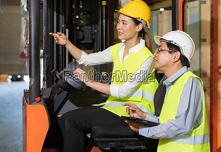 asiatische lagergabelarbeiter diskutieren mit manager