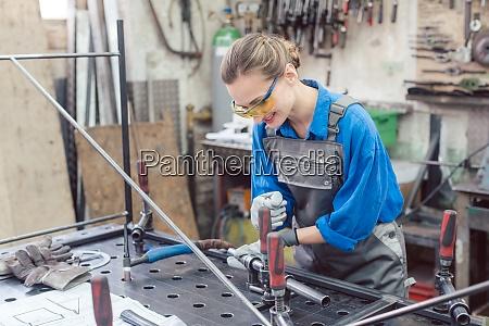 frau in metallwerkstatt mit werkzeugen und