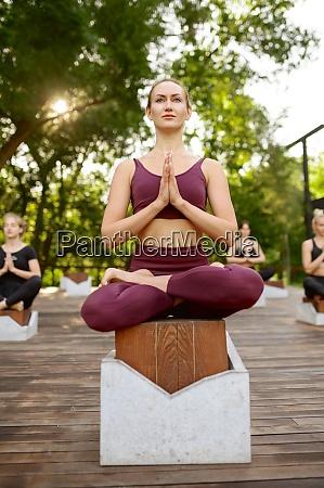 frauen entspannen in yoga pose gruppentraining