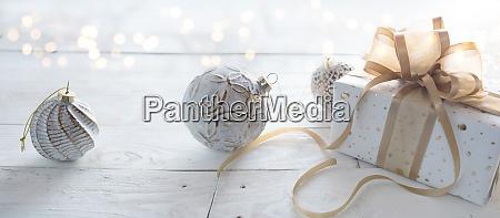 geschenkbox mit weissen weihnachtskugeln