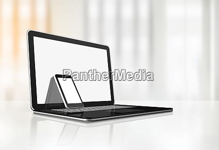 laptop und handy auf dem schreibtisch