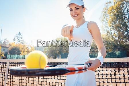 frau auf dem tennisplatz zeigt ihre