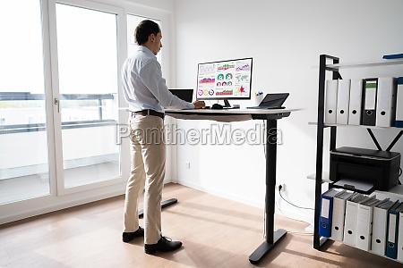 mann arbeitet am computer am stehtisch