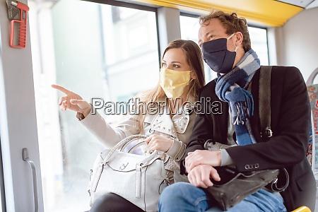 paar im OEpnv bus traegt masken
