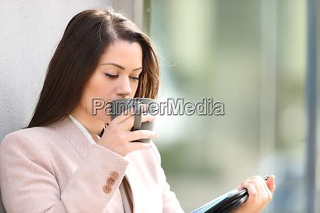 geschaeftsfrau trinkt kaffee und lesen informieren