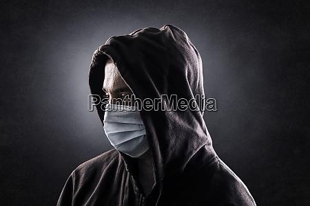 kapuzenmann traegt schutz gesichtsmaske gegen coronavirus