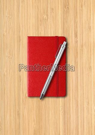 rotes geschlossenes notizbuch mit stift auf