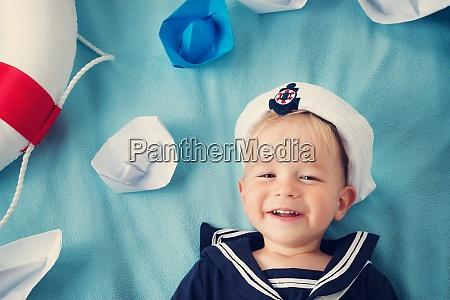 junge spielt mit papierschiffen