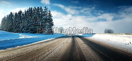 asphaltstrasse im schneebedeckten winter an schoenem