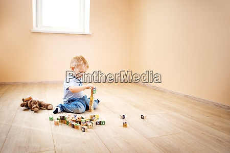 zweijaehriges kind sitzt mit holzwuerfeln auf