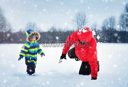 vater mit soehnen die bei schneefall