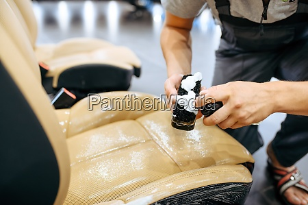 arbeiter mit spray befeuchtet autositz detaillierung
