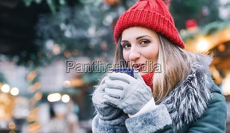 frau vor weihnachtsbaum auf wintermarkt trinken