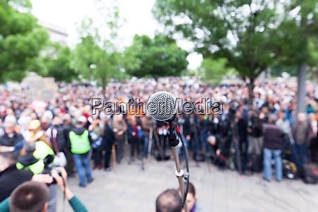 mikrofon im fokus gegen verschwommenen protest