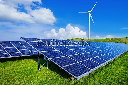 sonnenkollektoren und eine windkraftanlage gegen einen
