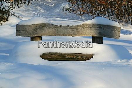 holzbank mit schnee bedeckt