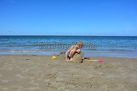 ein junge baut burg im sand