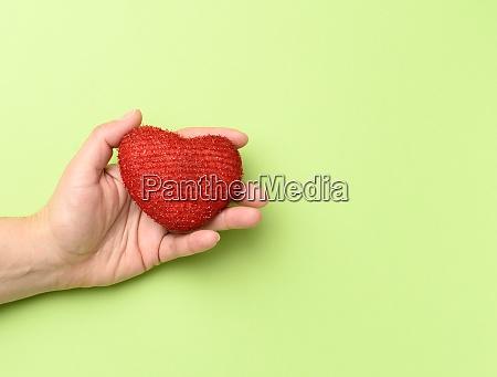weibliche haende halten rotes textilherz gruener