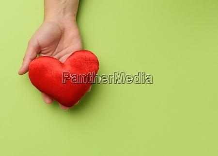 weibliche hand haelt rotes textilherz gruener
