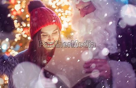 weihnachtsmann praesentiert schoene maedchen mit einem