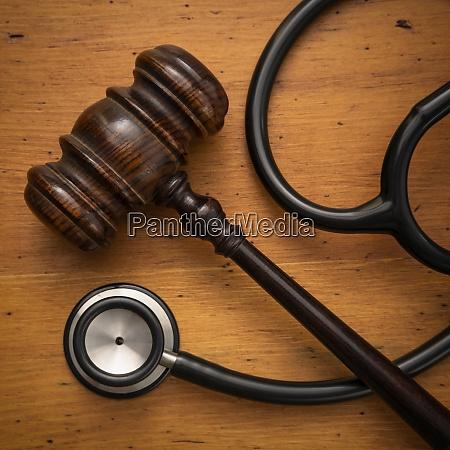 gavel und stethoskop auf holzhintergrund