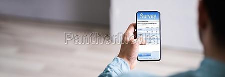 mann fuellt online umfrageformular aus