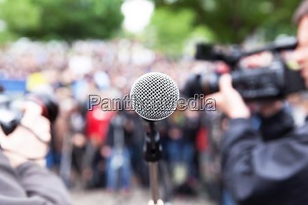 mikrofon im fokus bei strassenprotest verschwommener