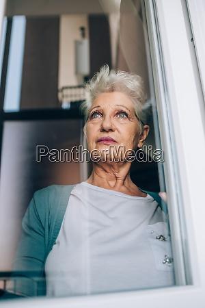 blick auf seniorin durch fenster