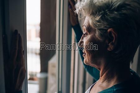 seniorin schaut aus wohnungsfenster
