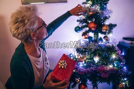 frau schmueckt weihnachtsbaum