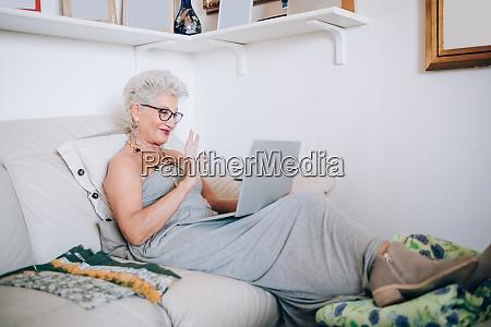 gesturing waving sitting using laptop kaukasische