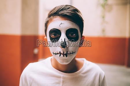 junge mit halloween schaedel gesicht farbe