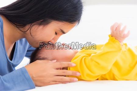mutter kuesst ihr neugeborenes in einem