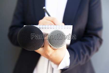 journalistin bei pressekonferenz oder medienveranstaltung notizen