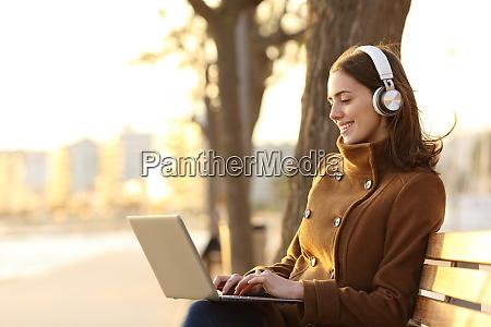 glueckliche frau traegt kopfhoerer mit laptop
