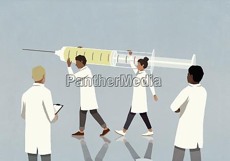 AErzte mit grosser covid impfstoffspritze
