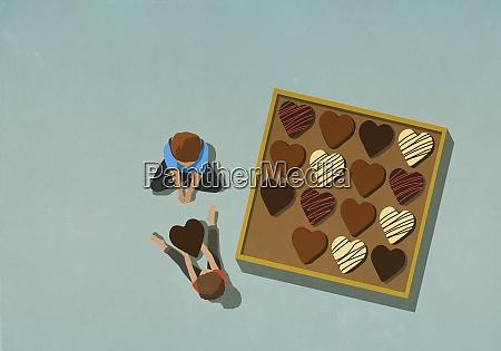 mann gibt herzform schokolade an frau