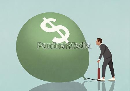 geschaeftsmann aufblasen dollar zeichen ballon mit