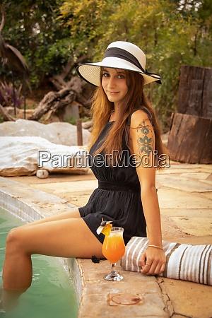 bruenette mit tattoo mit hut von