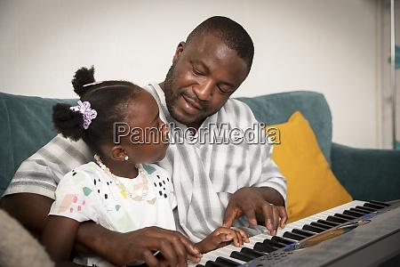 liebevollvater und tochter spielen klavier auf