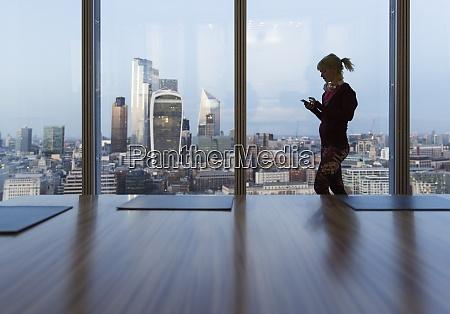 geschaeftsfrau mit smartphone im hochhausfenster london