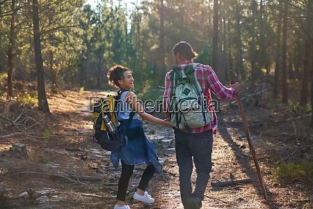 glueckliches junges paar mit rucksaecken wandern