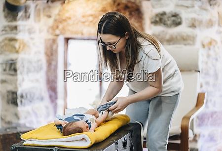 mutter wechselt windel des babys waehrend