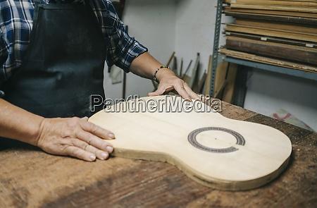 handwerker der gitarre herstellt waehrend er