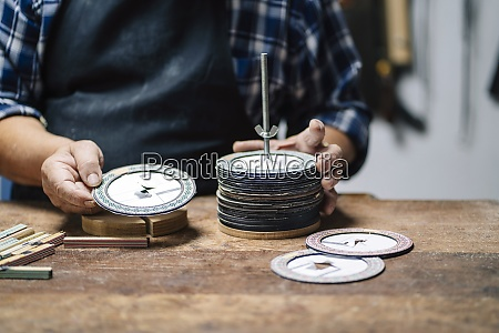 luthier waehlt papierscheibe aus waehrend er