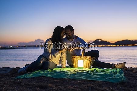 romantisches paar mit getraenken am strand