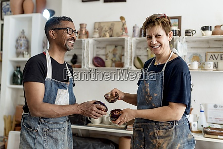 laechelnde kuenstler die keramik halten waehrend