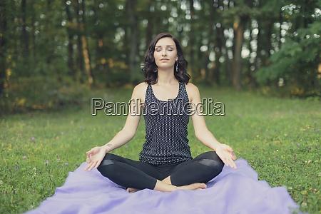 kroatien frau meditiert in lotusposition yoga